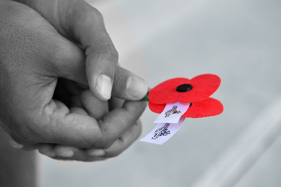 Anzac Commemorations - France and Belgium, Poppy in hands at Arras Memorial Cemetery