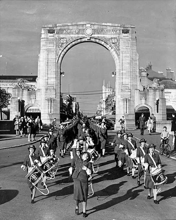 Women's Auxiliary Air Force (WAAF) drummers leading an Anzac parade through the Bridge of Remembrance, Cashel Street, Christchurch, in 1942. Image credit: © Air Force Museum of New Zealand MUS02168