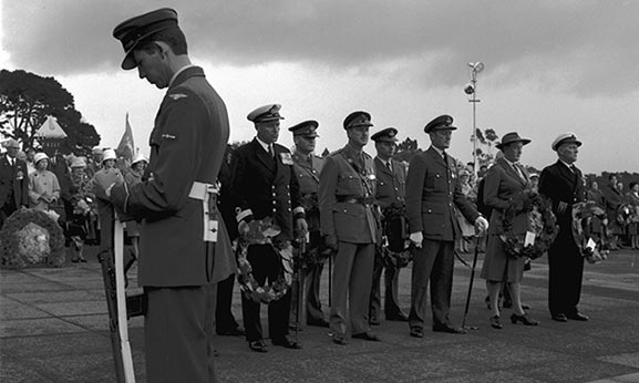 An RNZAF airman stands guard as part of the cenotaph party, while service representatives prepare to lay wreaths during the 50th Anniversary of Anzac Day parade at the Auckland War Memorial in 1965. Image credit: ©RNZAF Official WhG8220~65