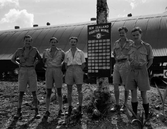 Group of Number 18 Squadron RNZAF officers with the New Zealand Fighter Wing scoreboard, Ondonga, New Georgia, November 1943. Image ref PR2367 ©RNZAF Official.