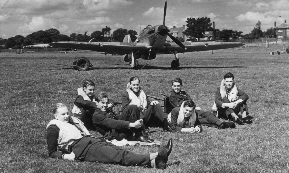 Group of pilots from 'B' Flight, Number 32 Squadron, resting on the grass in front of one of their Hurricanes at Royal Air Force Station Hawkinge. This is during the Battle of Britain. L-R: Pilot Officer RF Smythe, Pilot Officer K Gillman, Pilot Officer JE Proctor, Flight Lieutenant PM Brothers, Pilot Officer DH Grice, Pilot Officer PM Gardner, Pilot Officer AF Eckford. Image credit: Air Force Museum of New Zealand.