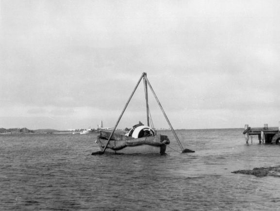 Salvage of Maritime Operational Conversion Unit Sunderland, NZ4111, after it was holed and sank in Te Whanga Lagoon, Chatham Islands. Engine being brought ashore in a snall boat.