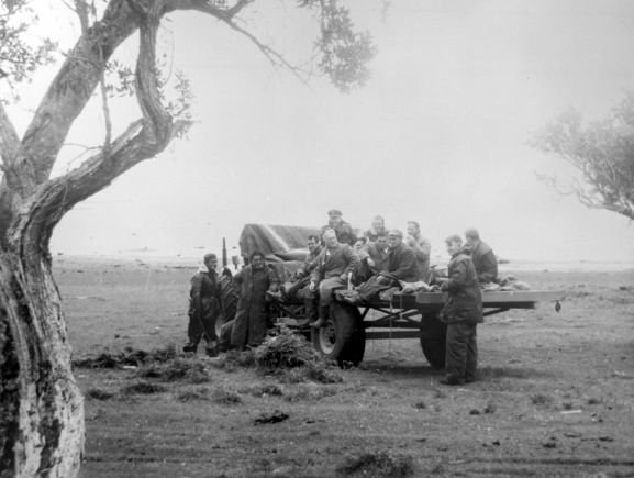 Salvage of Maritime Operational Conversion Unit Sunderland, NZ4111, after it was holed and sank in Te Whanga Lagoon, Chatham Islands. Members of the salvage party on a tractor's trailler.
