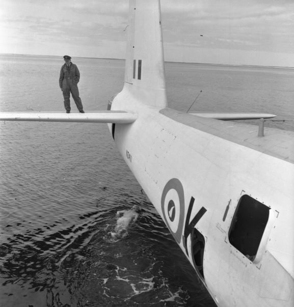 Salvage of Maritime Operational Conversion Unit Sunderland, NZ4111, after it was holed and sank in Te Whanga Lagoon, Chatham Islands. Wing Commander Henry Lionel Homer, Director of Aircraft Engineering, doing an exterior underwater inspection of the Sunderland, while Squadron Leader Robert Emery Weston (?) watches from the starboard horizontal stabiliser. NB. this negative deteriorating resulting in poorer image quality.