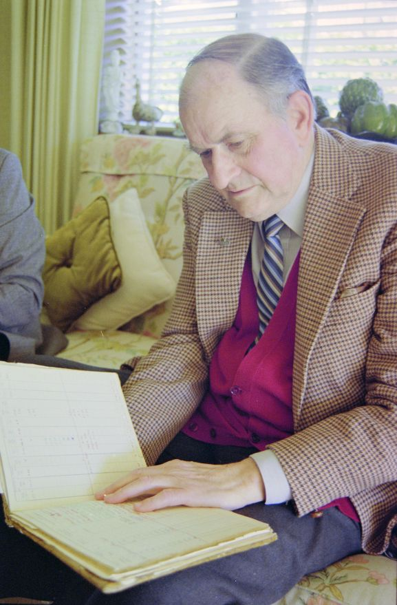 Portrait of Air Vice Marshal (retired) CL Siegert looking at his log book.