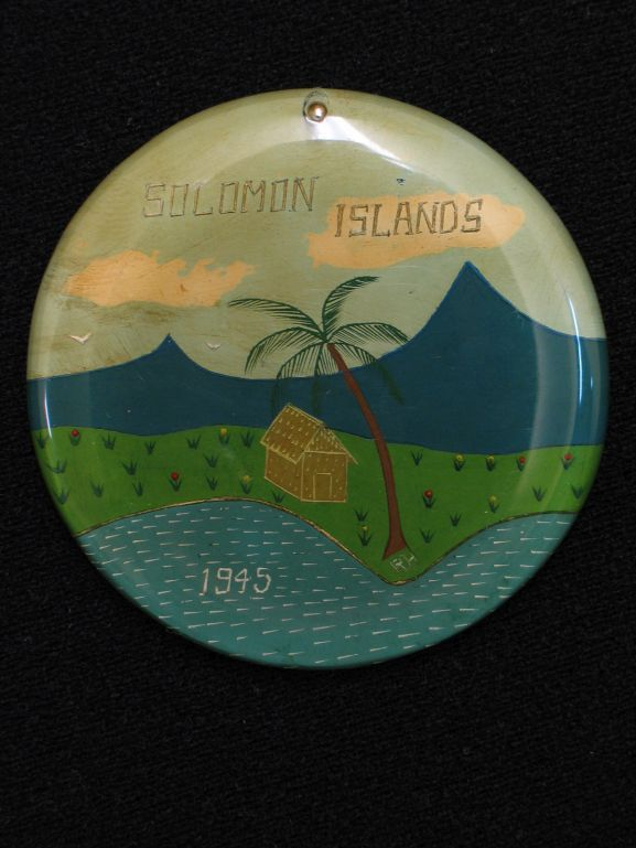"Round plexiglass pendant engraved with island beach scene - water, beach, hut, palm tree and mountains. ""SOLOMON ISLANDS "" engraved above mountains and ""1945"" in middle of water. Engraving has been highlighted by the reverse of pendant being painted. Made while with Royal New Zealand Air Force No. 12 Servicing Unit at Henderson Field, Guadalcanal."