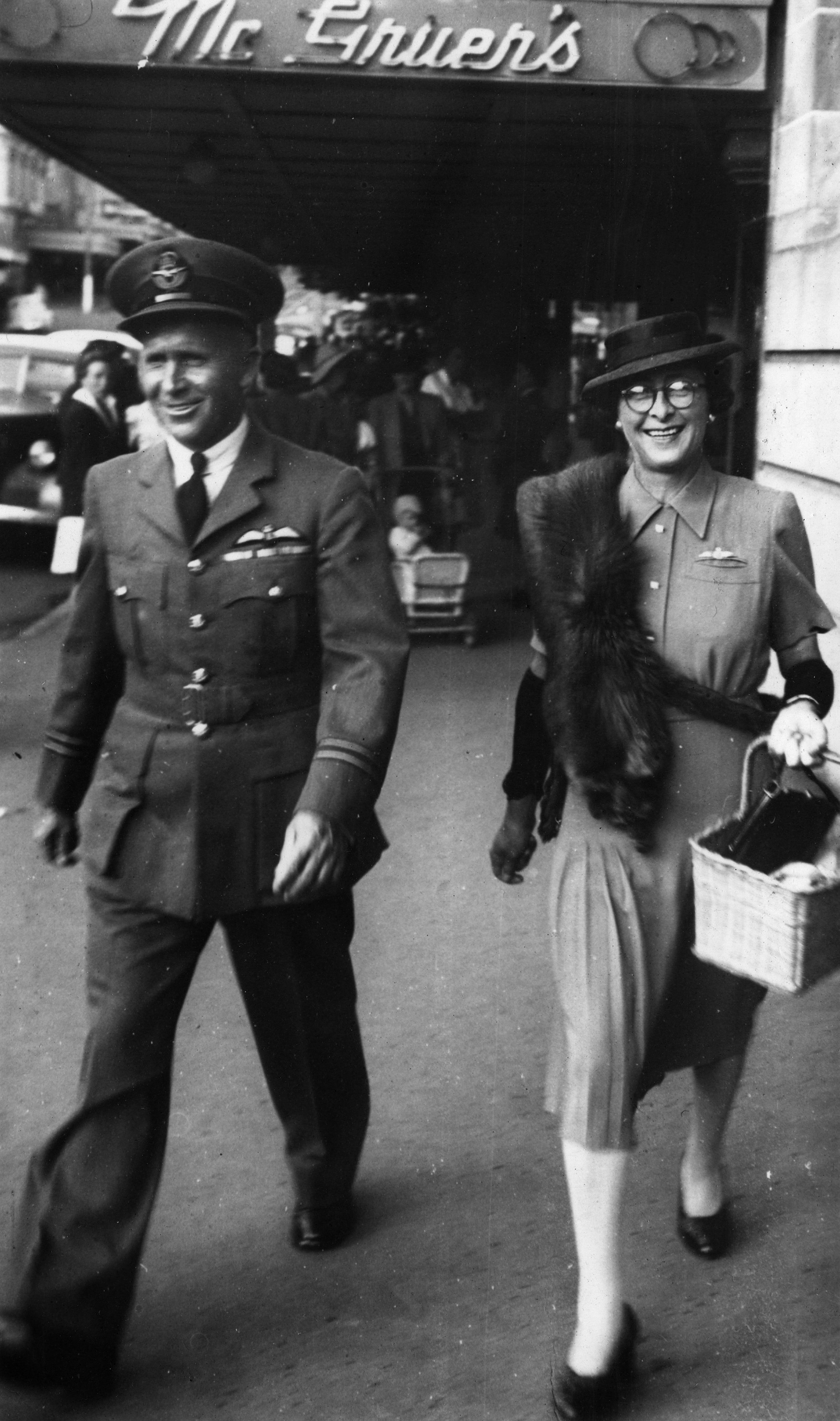 Flight Lieutenant HC Leese and his wife walking in a street in New Plymouth.
