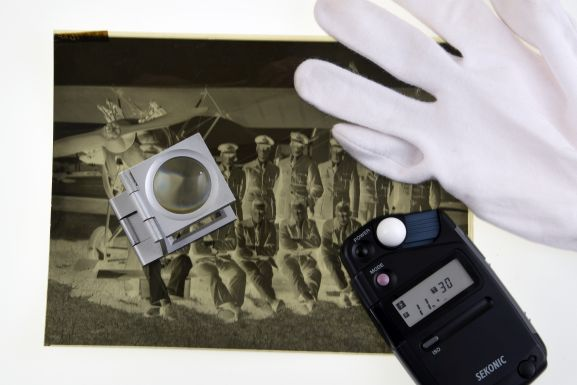 Still life featuring a negative, light meter, gloves and a magnifier. Air Force museum of New Zealand.