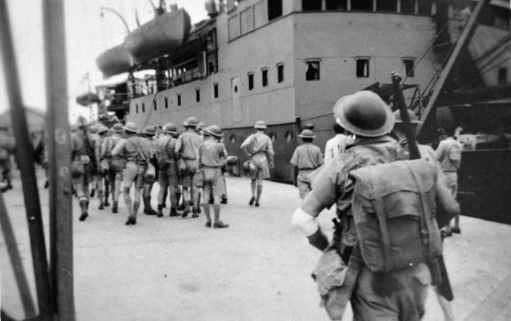 "Image from the Andrew Maguire personal album collection. ""Going aboard SS Darvel for [the] last time 9/2/42."" Personnel from No. 1 Aerodrome Construction Squadron on the dock in front of the ship SS Darvel during the evacuation from Singapore."