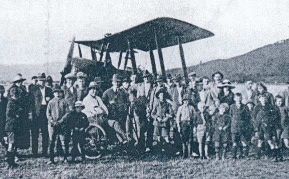 A crowd of people standing with the first aeroplane to cross Cook Strait, an Avro 504K of the Canterbury Aviation Company. Trentham, 25 August 1920. From the Murray Maxwell archive, Upper Hutt City Library Heritage Collections.