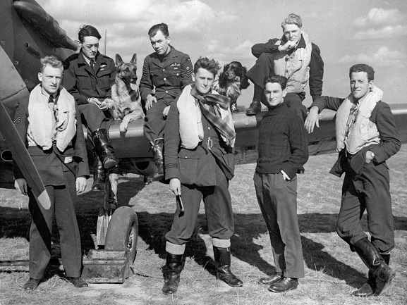 Group of pilots from Nos. 19 and 616 Squadron RAF pose with their dogs and a Spitfire at RAF Duxford, during the Battle of Britain, 1940. L-R: On wing; Brian Lane, 'Flash' the Alsatian, 'Grumpy' Unwin, 'Rangy' the Spaniel, Noel Brinsden (NZ). Standing; Bernard Jennings, Colin MacFie, Billy Burton, Philip Lackrone (American). Image ref PR8796a, RNZAF Official.