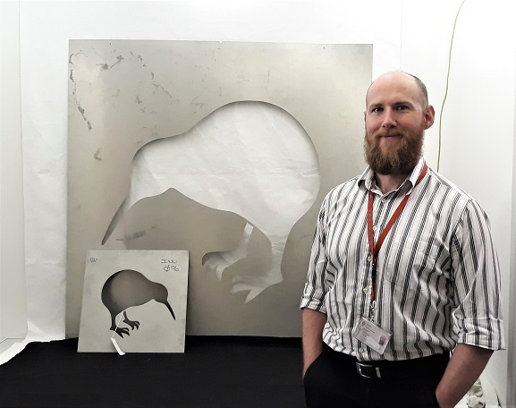 Collections Technician Murray McGuigan with the original stencils for the application of the RNZAF kiwi roundel, now in the collection of the Air Force Museum of New Zealand.