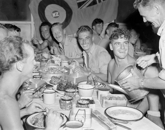 Group of airmen receiving Christmas dinner, served by officers, as is traditional at Christmas time.  Bougainville, 1944. Image ref PR4676, RNZAF Official.