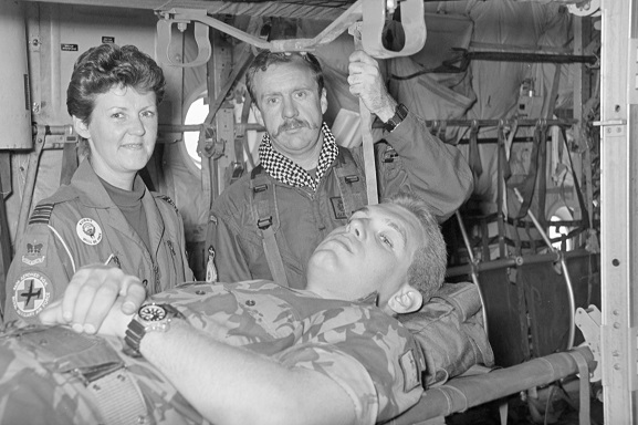 Corporal John Felton acts as patient on a stretcher in a No. 40 Squadron Hercules fitted out for aeromedical evacuation, with Squadron Leader Pauline Gwyther (No. 4626 Aeromedical Squadron, RAF) and Air Loadmaster Gary Porteous. Believed to be at Riyadh, Saudi Arabia, Feb-Mar 1991. Image ref PD12-28-91, RNZAF Official.