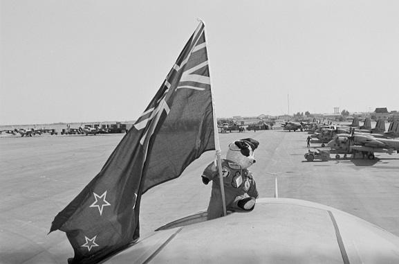 No. 75 Squadron RNZAF mascot, Henry Fanshaw, 'on deployment' with No. 40 Squadron, proudly waving a New Zealand flag atop a 40 Squadron Hercules. Riyadh, Saudi Arabia. In the background are US Army Grumman Mohawk aircraft. Operation Fresco, Feb-Mar 1991. Image ref. PD13-9-91, RNZAF Official.