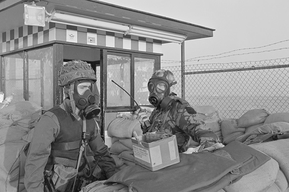 RNZAF Flight Lieutenant Ken Cunningham (right) and a soldier wearing gas masks at a guard post during a Scud missile alert at King Khalid International Airport, Riyadh, Saudi Arabia. Feb-Mar 1991. Image ref PD15-9-91, RNZAF Official.
