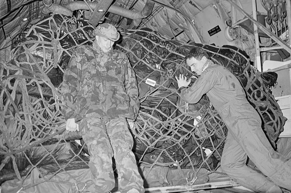 Operation Fresco. Flight Sergeant Stephen Skudder (right) and SSE Fred Bias (RAF) loading freight into the back of a No. 40 Squadron Hercules at King Khalid International Airport, Riyadh, Saudi Arabia. Feb-Mar 1991. Image ref PD18-24-91, RNZAF Official.