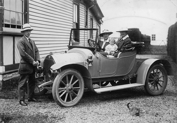 Canterbury Aviation Company Chief Flying Instructor, Cecil Hill standing at the front of a car with two women and a baby, at Sockburn Aerodrome, 1918. Image ref MUS9709010, Air Force Museum of New Zealand.
