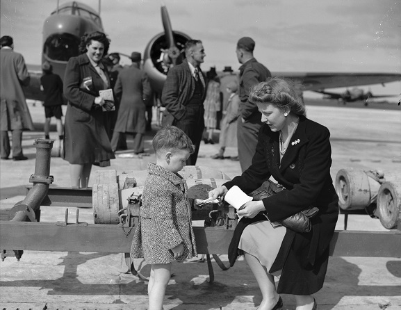 Mother and child beside a bomb trolley during an open day at RNZAF Station, Whenuapai, 1944. Image ref PR4088, RNZAF Official.